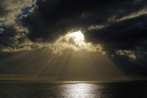 Sun breaking through clouds over ocean